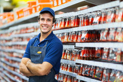 Hardware store salesman. Handsome hardware store salesman standing next to fasteners shelf Royalty Free Stock Images