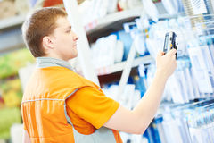 Hardware store salesman worker with arcode scanner. Young male caucasian salesman or salesperson scanning barcode of goods in hardware store Stock Photography