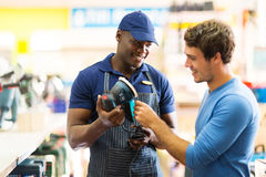 Hardware store worker customer. Friendly hardware store worker showing customer a sander Royalty Free Stock Photography