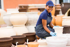 Hardware store worker. Happy african female hardware store worker selling flower pot Royalty Free Stock Photography