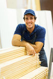 Hardware store worker. Happy hardware store worker standing next to stacked wood Royalty Free Stock Images