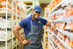 Hardware store worker. Smiling african hardware store worker standing by the fasteners aisle royalty free stock photography