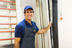Hardware store worker. Standing next to wood board cutting machine Stock Images