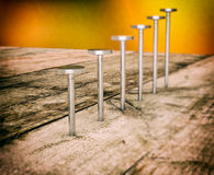 Hardware tools, steel nails. Set of steel nails on a wooden table (3d render royalty free illustration