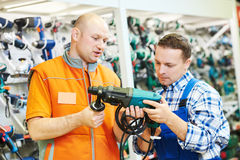 Hardwarer store worker or buyer. Sales assistant at work. male hardware store worker helps to choose drill or perforator to buyer customer Royalty Free Stock Photos