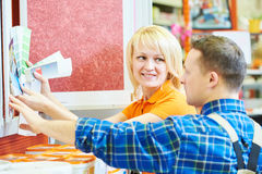 Hardwarer store worker or buyer. Sales assistant at work. smiling female hardware store worker helps to choose paint for painting to buyer customer with color Royalty Free Stock Photos