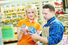 Hardwarer store worker or buyer. Sales assistant at work. smiling female hardware store worker helps to choose paint for painting to buyer customer Royalty Free Stock Image