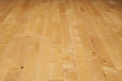 Hardwood basketball court floor viewed from a low angle. A basketball court floor made of maple hardwood viewed at a low angle Stock Photo