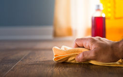 Hardwood floor cleaning and manteinance. Male hand applying wood care products and cleaners on hardwood floor surface Stock Photo