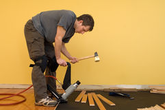 Hardwood floor installation. Man installing tongue and groove hardwood floor Royalty Free Stock Images