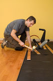 Hardwood floor installation. Man installing tongue and groove hardwood floor Stock Photo