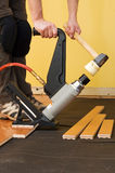 Hardwood floor installation. Man installing tongue and groove hardwood floor Stock Image
