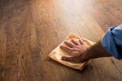 Hardwood floor manteinance. Male hand cleaning and rubbing an hardwood floor with a microfiber cloth Stock Photography
