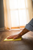 Hardwood floor manteinance. Male hand cleaning and rubbing an hardwood floor with a microfiber cloth Stock Image