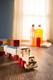 Hardwood floor safe cleaning. Wooden toy train with wood cleaner products on parquet next to a window royalty free stock photo
