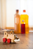 Hardwood floor safe cleaning. Wooden toy train with wood cleaner products on parquet next to a window royalty free stock image