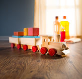 Hardwood floor safe cleaning. Wooden toy train with wood cleaner products on parquet next to a window royalty free stock images