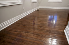 Hardwood Floors - Refinished. A gleaming oak hardwood floor shines after being refinished in a rich dark tone with a glossy protective finish. Freshly painted Stock Photo
