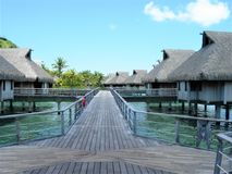 Hardwood path to over water Bungalows Bora Bora resort. Over water hardwood path to bungalows Bora Bora French Polynesia with clear blue skies and clear water stock images
