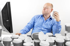 Hardworking business man drinks too much coffee Royalty Free Stock Photo