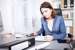 Hardworking businesswoman sitting writing a report Royalty Free Stock Photo
