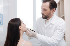 Hardworking caring plastic surgeon ensuring preciseness Stock Images