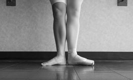 The hardworking disciplined ballerina ballet dancer warming up in her pointe shoes and bare feet, displaying the behind the scenes. Of a dancer at the barre royalty free stock image