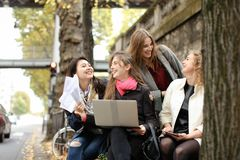 European students learning with laptop and papers, sitting on be Royalty Free Stock Images