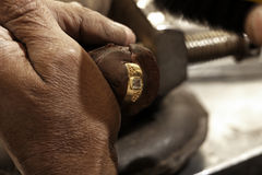 Hardworking Goldsmith. Working on an unfinished 22 carat gold ring with his aged hands Royalty Free Stock Image