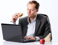 Hardworking man eating at his desk royalty free stock image