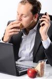 Hardworking man eating at his desk royalty free stock photos