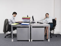 Hardworking Man And Relaxed Woman in office Stock Images