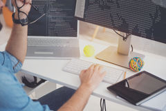 Hardworking man using laptop and computer in an office Stock Photography