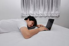 Hardworking people concept. Tired overworked young Asian man sleeping with computer laptop on the bed in bedroom royalty free stock photography