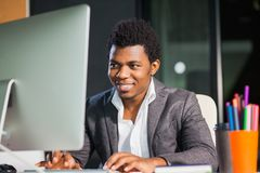 Hardworking smiling afroamerican at office look at computer monitor. Young handsome black man royalty free stock photography