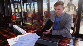 Young student preparing before exam in fast motion at cafe with papers and tablet. Hardworking student preparing before exam in fast motion at cafe with papers stock footage