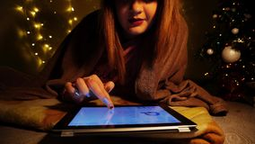 Beautiful woman reciting poem on tablet. Hardworking student reading aloud Christmas poesy on tablet. Charming girl whispering piece of poetry. Concept of Royalty Free Stock Photography