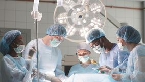 Hardworking team of surgeons at work in operating room. stock video