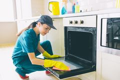 Hardworking woman sits in squad position and cleans door of stove. She is professional in cleaning. Girl wears gloves. Cap and uniform royalty free stock image
