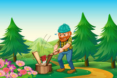 A hardworking woodman chopping the wood near the garden at the h Royalty Free Stock Image