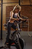 Hardworking young beautiful girl doing exercise on bicycle training apparatus stock photo