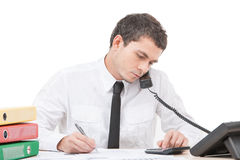 Hardworking young man talking on phone. Stock Photos