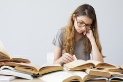 Hardworking student studying. Hardworking young student studying book Royalty Free Stock Photos