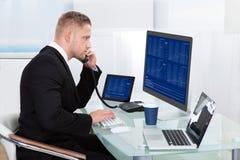 Hardworking zakenman bij zijn bureau Stock Afbeelding
