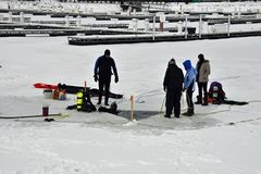 Hardy scuba divers on the frozen lake in January. Under grey skies Royalty Free Stock Photos