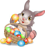 Hare and Easter. Rabbit in front of a basket with Easter eggs Royalty Free Stock Photography