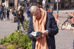 Hare Krishna member looking in a book in public street. Stock photo stock photo