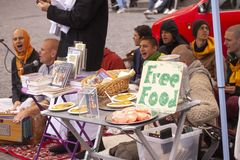 Hare Krishna members singing and playing in the street with sign offering free food. Stock photo stock image