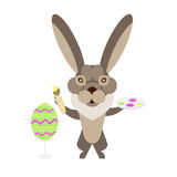 Hare painting easter eggs Royalty Free Stock Photos