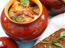 Hare wild rabbit with vegetables Goulash in Copper Pot on blue Wooden table, roasted beef meat with carrot, leek, onion in round c. Eramic pot with bread on Royalty Free Stock Photo